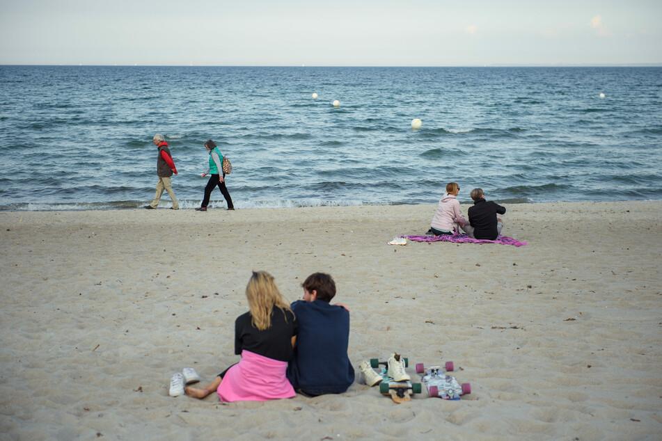 Paare sitzen und gehen in einigem Abstand zueinander am Strand von Scharbeutz.