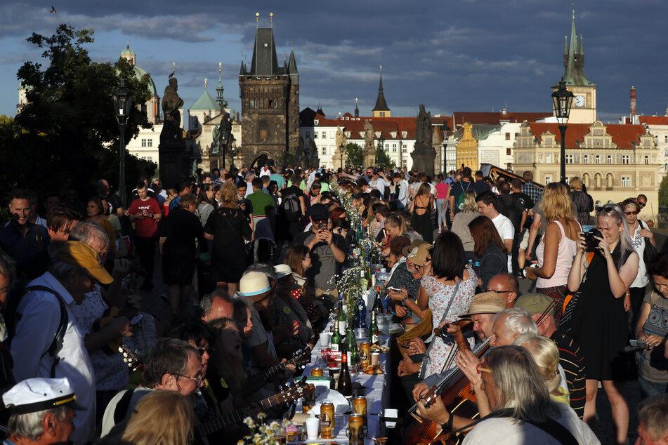 30. Juni, Prag: Anwohner sitzen zum Essen an einem 500 Meter langen Tisch auf der mittelalterlichen Karlsbrücke, nachdem die Einschränkungen während der Corona-Pandemie gelockert wurden.