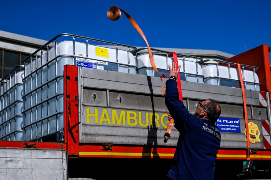 Ein Mitarbeiter der Feuerwehr verpackt auf dem Betriebsgelände der Beierdorf AG Paletten mit Desinfektionsmitteln auf einem Einsatzfahrzeug.