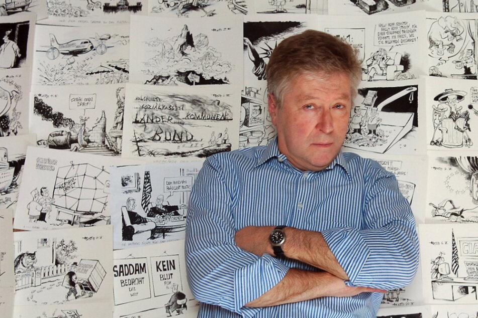Der Karikaturist Horst Haitzinger lehnt in seiner Wohnung in München an einer Wand mit seinen Karikaturen. (Archiv)