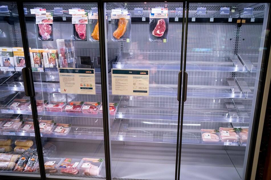 Das Kühlregal in einem Supermarkt ist zum Teil leer.