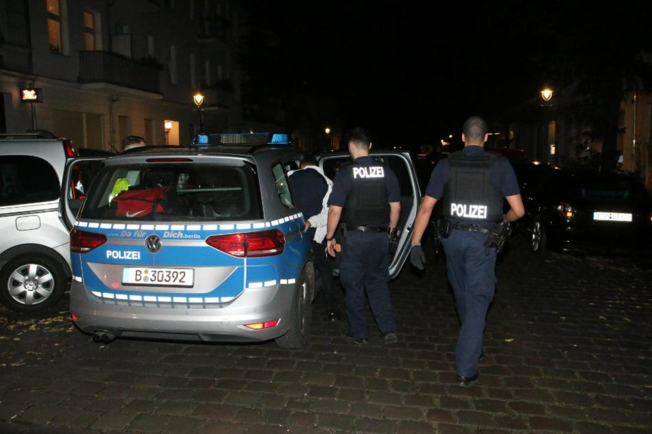 Polizisten führen einen der Tatverdächtigen ab.