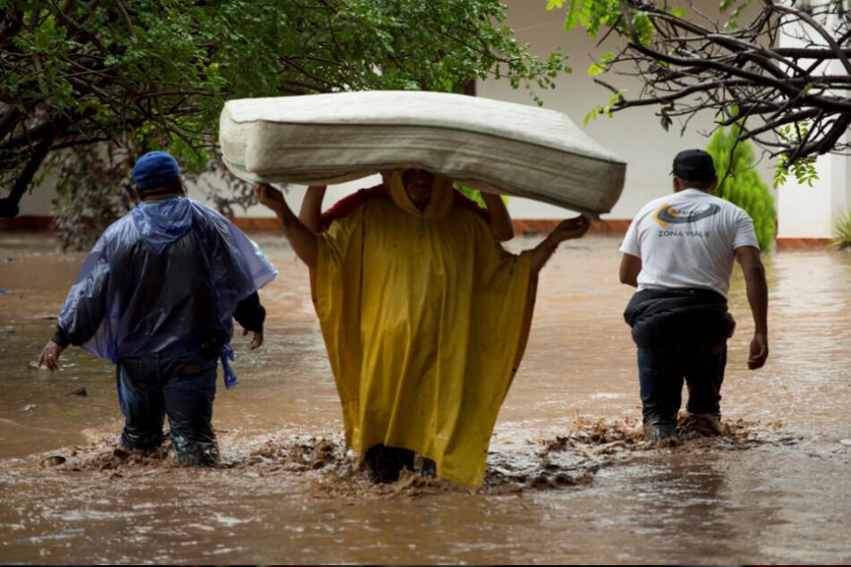 Guatemala, Agua Blanca: Zwei Männer tragen eine Matratze durch eine überschwemmte Straße.