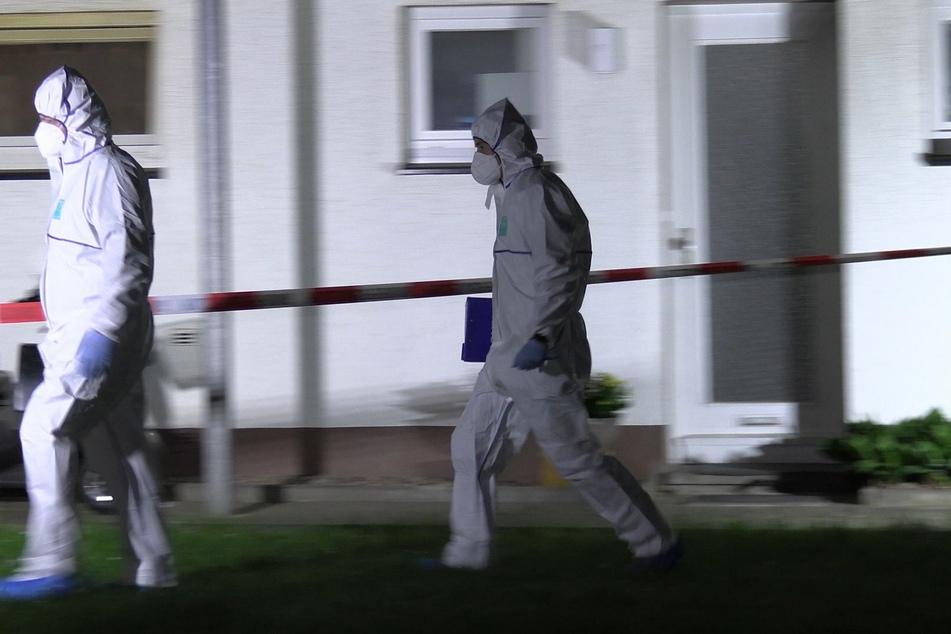 Beamte in Schutzanzügen am Tatort.