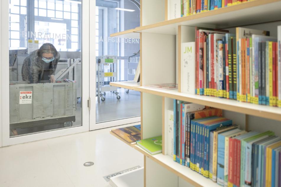 Eine Mitarbeiterin legt in der Stadtbibliothek Stuttgart am Mailänder Platz ein Buch in eine Quarantänebox. Die Bibliothek ist für Besucher größtenteils geschlossen - alleine zum Abholen von Medien darf ein kleiner Bereich des Erdgeschosses betreten werden.