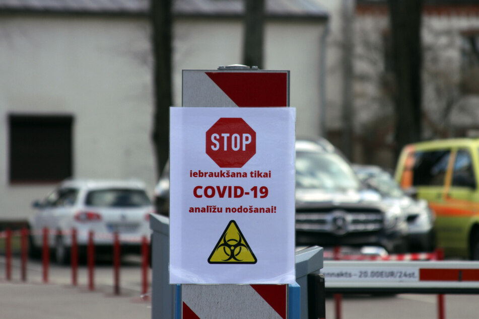 """Ein Schild mit einem Stoppzeichen und der Aufschrift """"Iebrauksana tikai Covid-19 Analizu nodosanai"""" (Einfahrt nur zur Abgabe von Covid-19 Analyse) hängt an einer Schrankenanlagen an der Einfahrt zur Teststation an der Pauls-Stradins-Universitätsklinik in Riga. Menschen mit Covid-19 Verdacht werden hier getestet."""