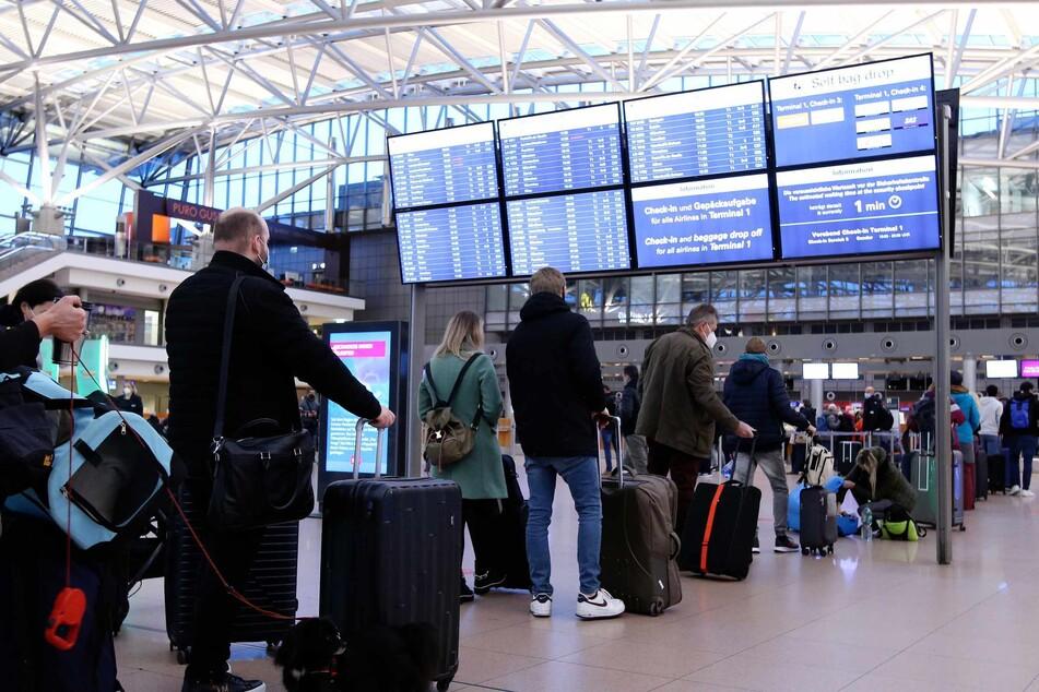 Reisende stehen vor dem Check-In-Schalter in einer Schlange.