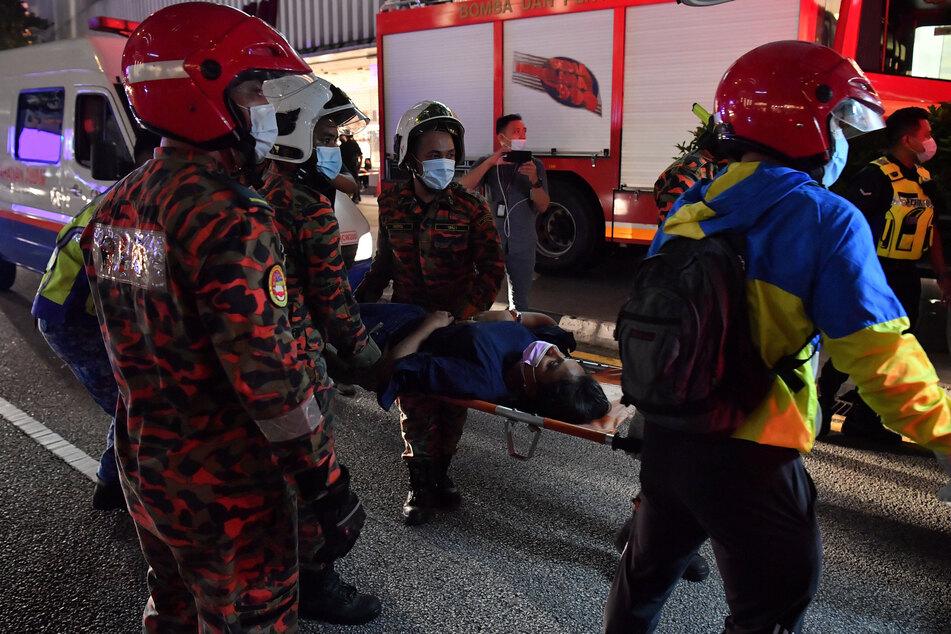 Rettungskräfte tragen einen verletzten Fahrgast, nachdem zwei Light Rail Transit (LRT)-Züge in der Nähe der Station Kampung Baru zusammengestoßen sind.