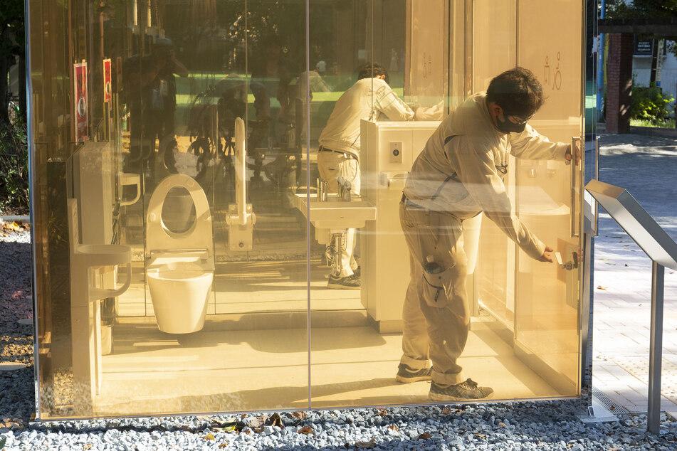 Ein Mann schließt die Tür einer neu installierten öffentlichen Toilette mit transparenten Wänden, die im Yoyogi Fukamachi Mini Park im Bezirk Shibuya steht.