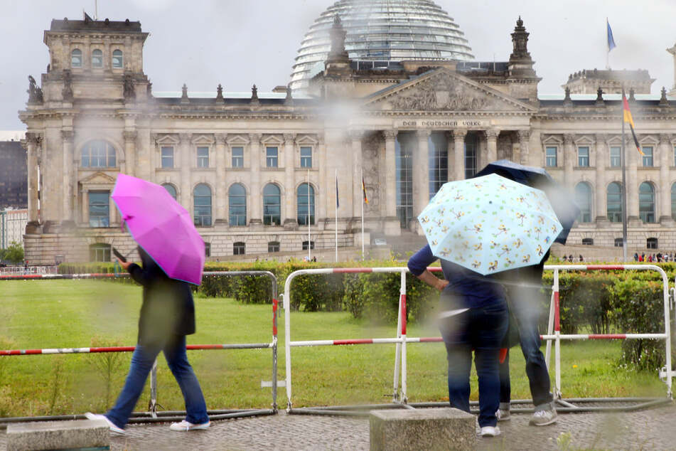 Passanten trotzen im Regierungsviertel dem Regen mit einem Regenschirm. In Berlin dürfte es nass werden.