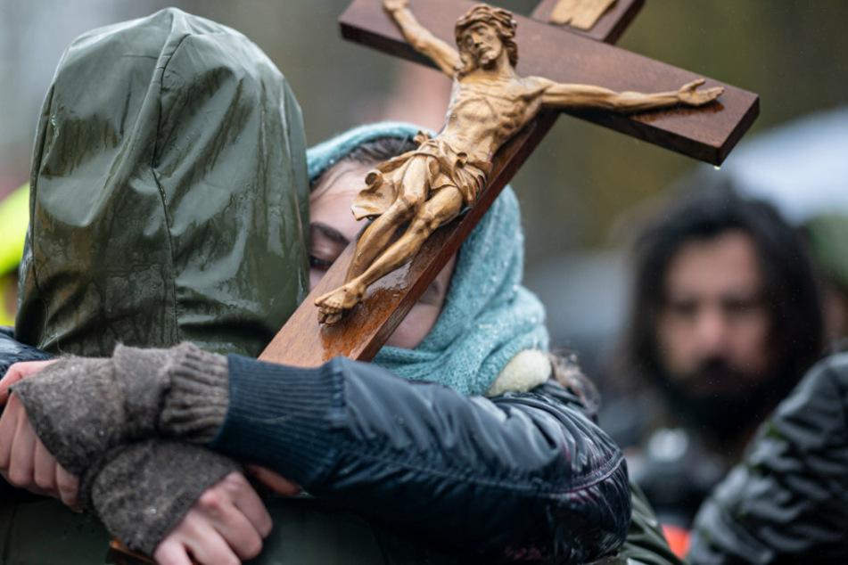 Zwei Teilnehmer der Demonstration gegen die Corona-Einschränkungen der Bundesregierung am Brandenburger Tor umarmen sich und halten ein Holzkreuz in der Hand.