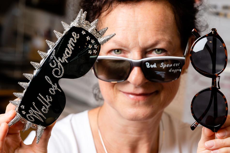 """Optikerin Edith Plüschke (53) mit einer kleinen Auswahl der Promi-Brillen. Die Ausstellung """"Walk of Frame"""" gibt's im Geschäft noch bis Mitte September zu sehen."""