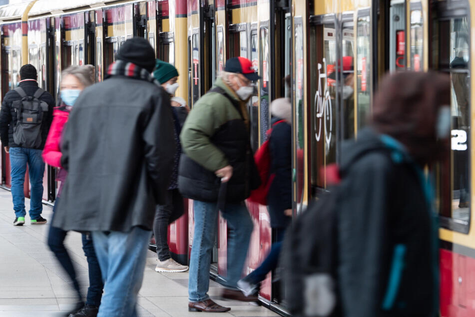 Fahrgäste mit Mund-Nasen-Bedeckungen steigen am Bahnhof Friedrichstraße in Mitte in eine S-Bahn ein.