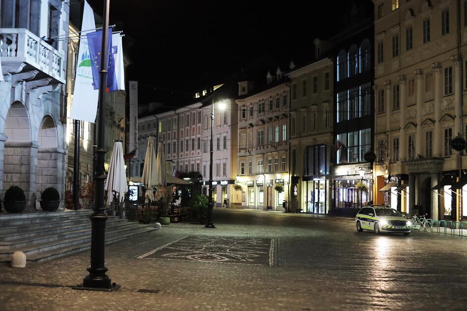Ein Polizeiauto fährt durch eine menschenleere Straße in Ljubljana. Aufgrund steigender Corona-Zahlen gelten in dem Land ab 15. Juli verschärfte Corona-Regeln.