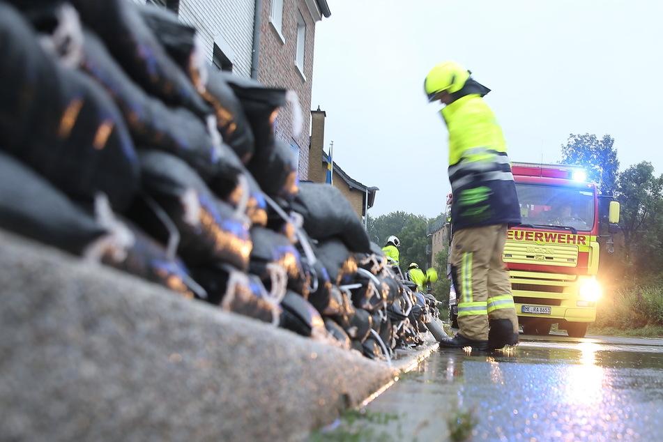 Einsatzkräfte der Feuerwehr errichten am Straßenrand eine Wassersperre aus Sandsäcken.