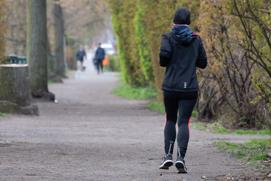 Eine Frau läuft dick eingepackt am Weigandufer in Neukölln entlang. Der Frühling in Berlin bleibt nass und frisch.