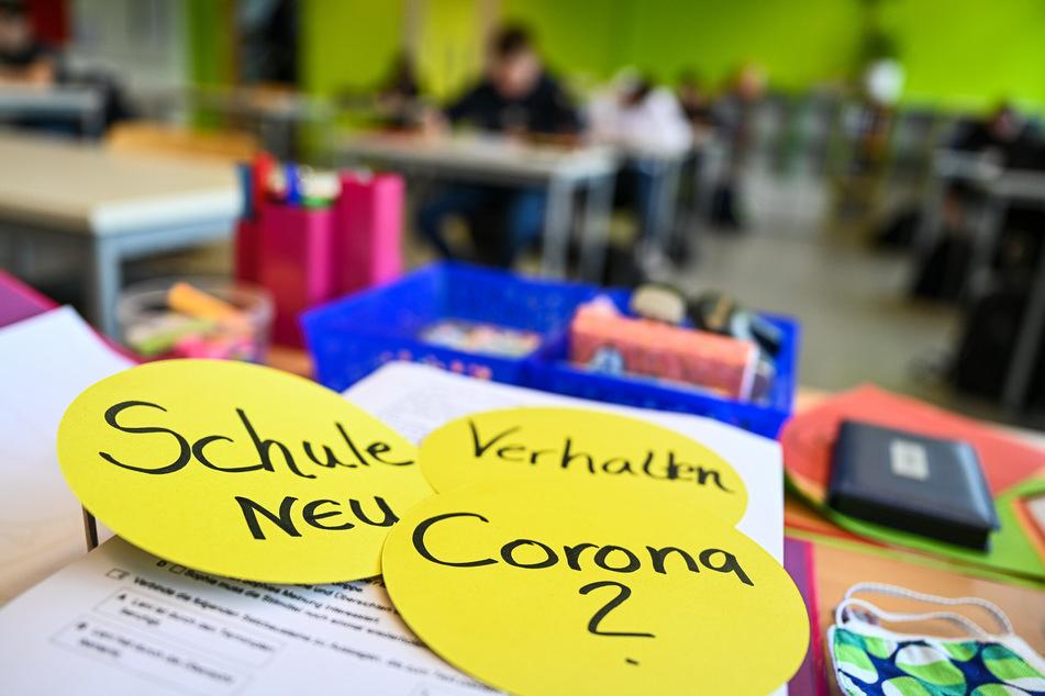 """Schüler einer Abschlussklasse sitzen im Klassenzimmer, während auf dem Lehrerpult drei runde Schilder mit der Aufschrift """"Schule neu"""", """"Verhalten"""" und """"Corona"""" liegen."""