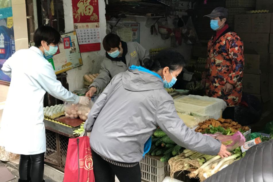 Bewohner der chinesischen Stadt Wuhan kaufen Gemüse in einem Laden.