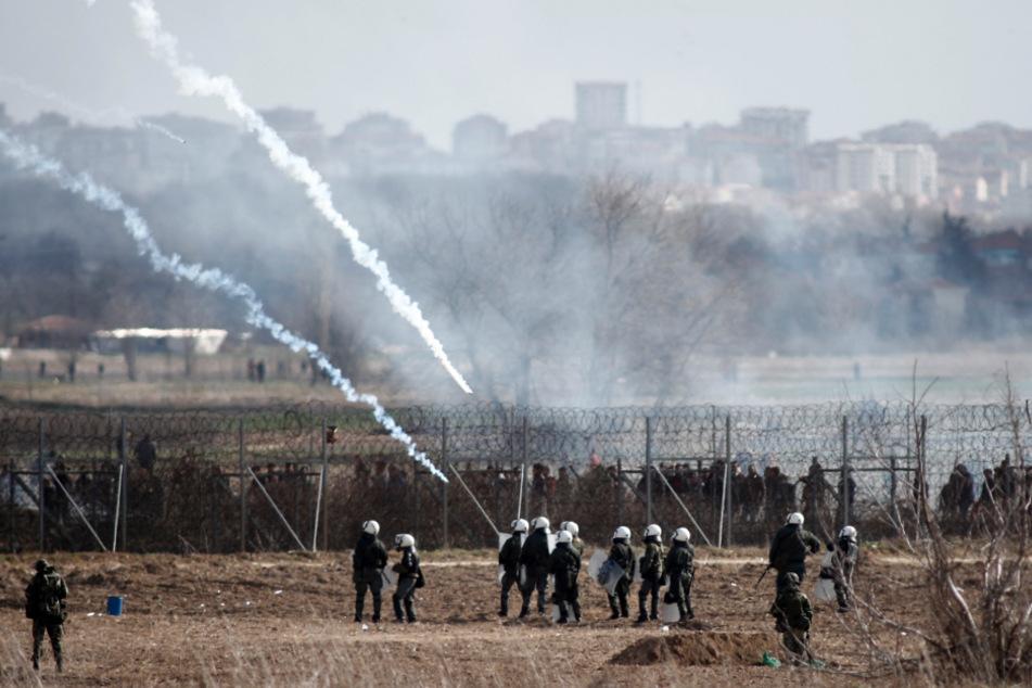 Griechische Polizisten stehen in der Nähe eines Grenzzauns zur Türkei, während bei Zusammenstößen zwischen Grenzschützern und Migranten Tränengas abgefeuert wird.