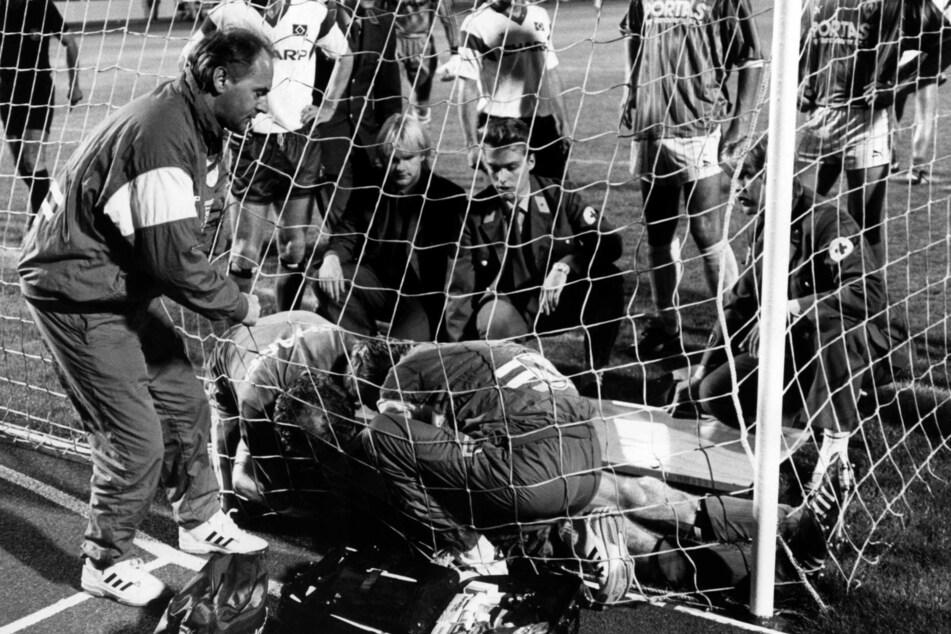 HSV-Abwehrspieler Ditmar Jakobs (verdeckt, unten) liegt im Torgehäuse und Helfer und HSV-Trainer Willi Reimann (l) versuchen ihn zu befreien. Ein Karabinerhaken hatte sich in seinen Rücken gebohrt.