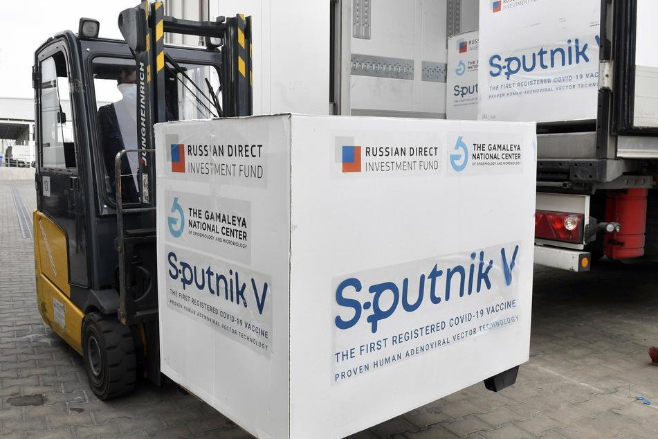 Kisten mit Dosen des russischen Corona-Impfstoffs Sputnik V werden in einem Lagerhaus des ungarischen Pharmagroßhändlers Hungaropharma aus einem Lastwagen geladen.