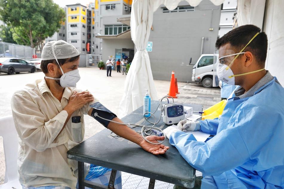 """Ein Mann mit Mundschutz bekommt in der Nähe des Wohnkomplexes """"Toh Guan Dormitory"""" eine Gesundheitskontrolle von einem Arzt."""