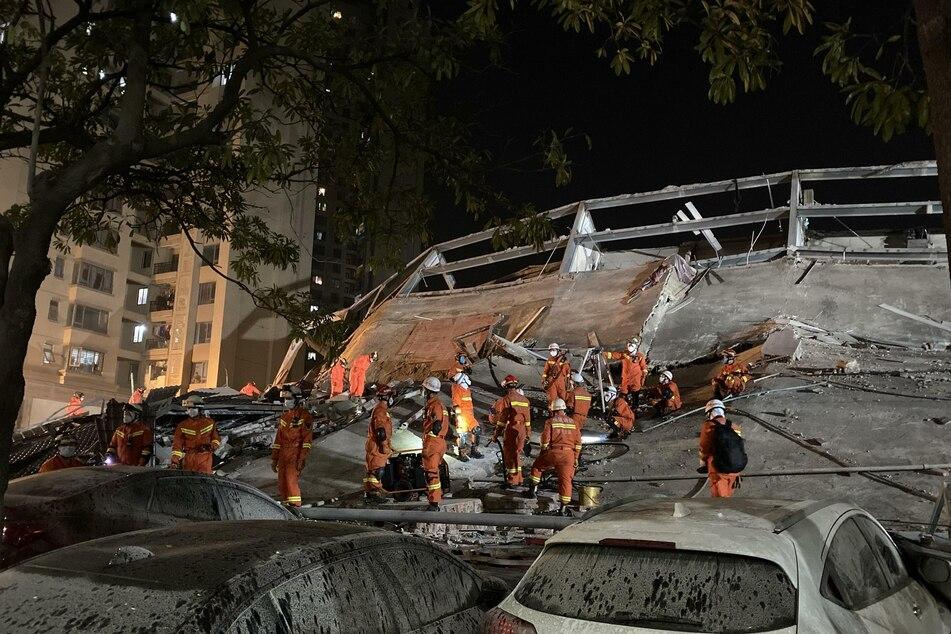 Rettungskräfte arbeiten an der Unfallstelle des eingestürzten Hotelgebäudes.