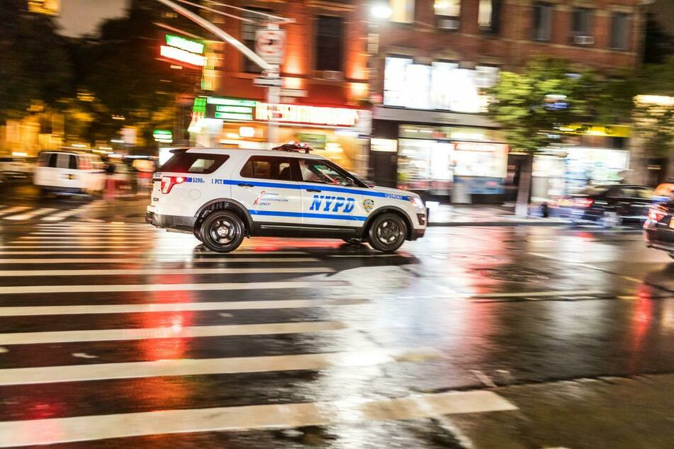 NYPD patrol car racing down the street (stock image).