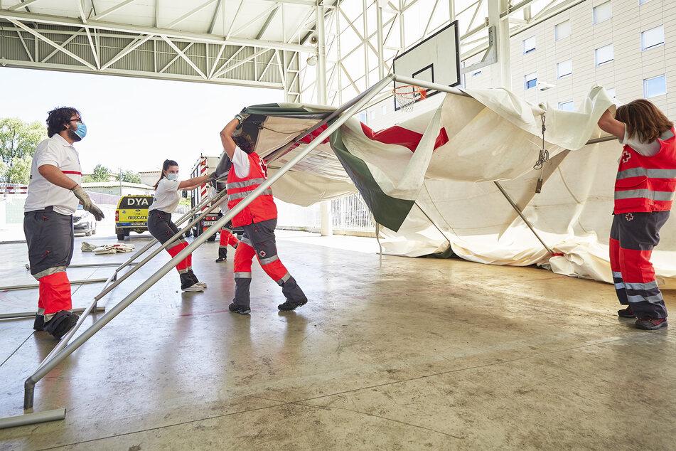 Mitarbeiter des Roten Kreuzes errichten im Hof eines Gymnasiums in Pamplona ein Zelt zur Durchführung von Corona-Tests.