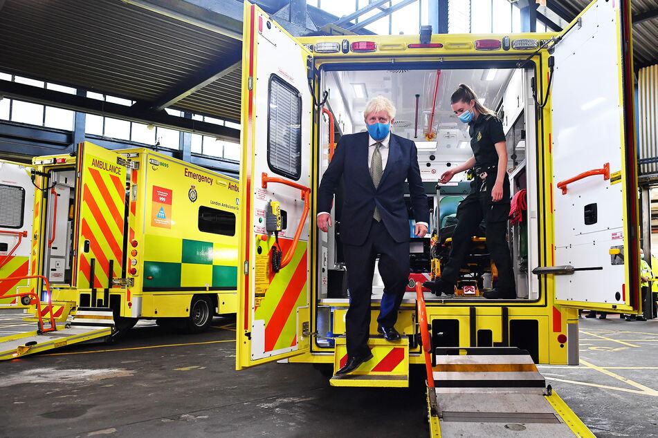 Boris Johnson, Premierminister von Großbritannien, trägt eine Stoff-Maske und steigt während eines Besuchs im Hauptquartier des London Ambulance Service NHS Trust mit einer Sanitäterin aus einem Krankenwagen.