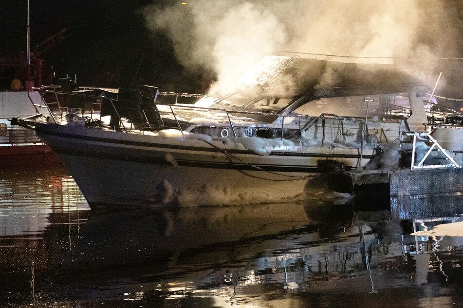 Das Foto zeigt das qualmende Wrack der Yacht im Sportboothafen in Frankfurt-Griesheim.