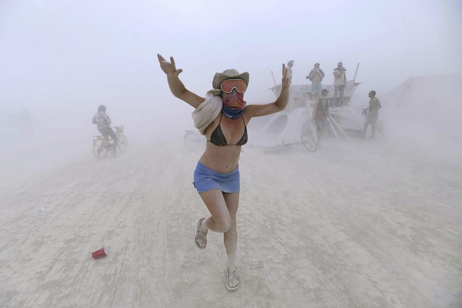 Eine Frau tanzt während eines Sandsturms beim Burning-Man-Festival 2017. Aufgrund der Corona-Pandemie ist das legendäre Festival erneut abgesagt worden.