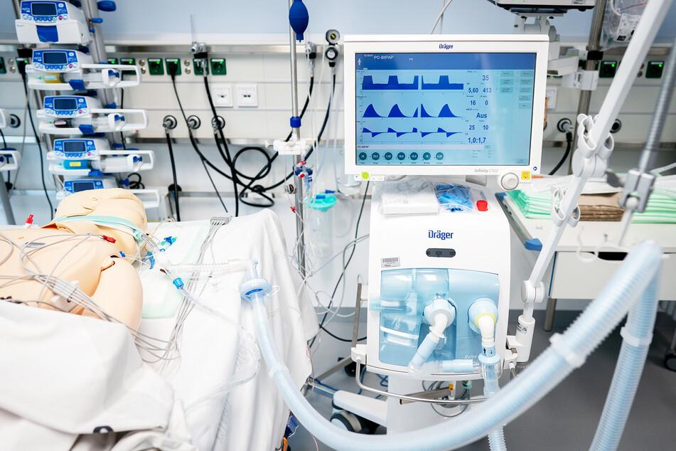 Ein Beatmungsgerät der Firma Dräger steht an einem Krankenhausbett.