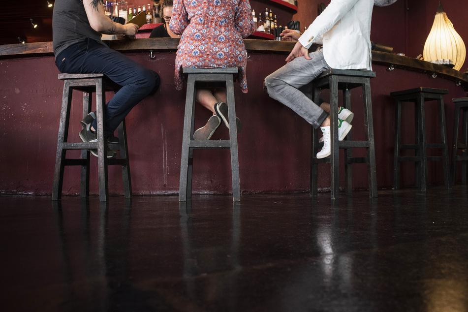 Gäste sitzen an einer Bar.