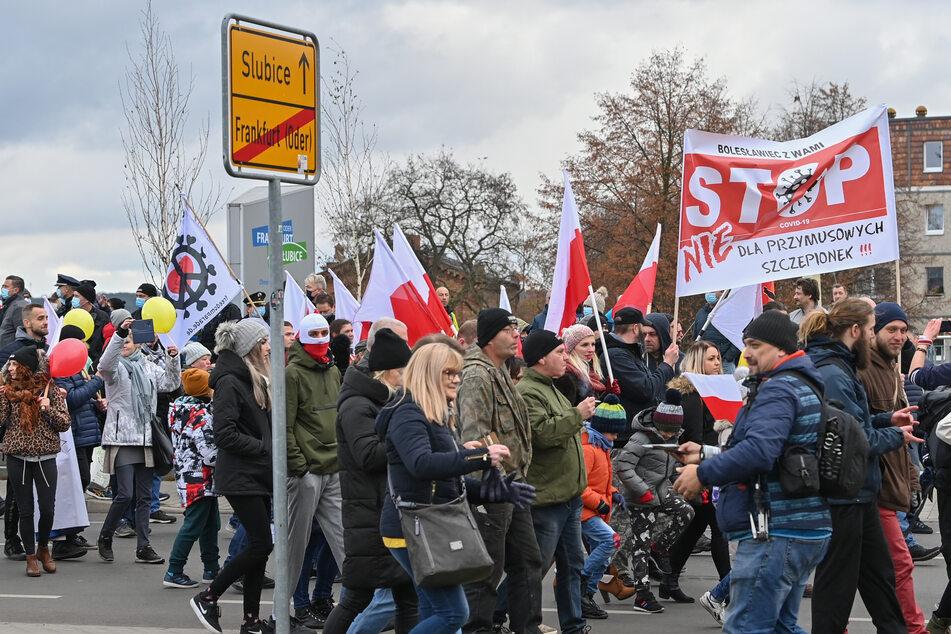 Aus dem polnischen Slubice gehen Teilnehmer einer Demonstration gegen Corona-Maßnahmen über den Grenzübergang Stadtbrücke nach Frankfurt (Oder).