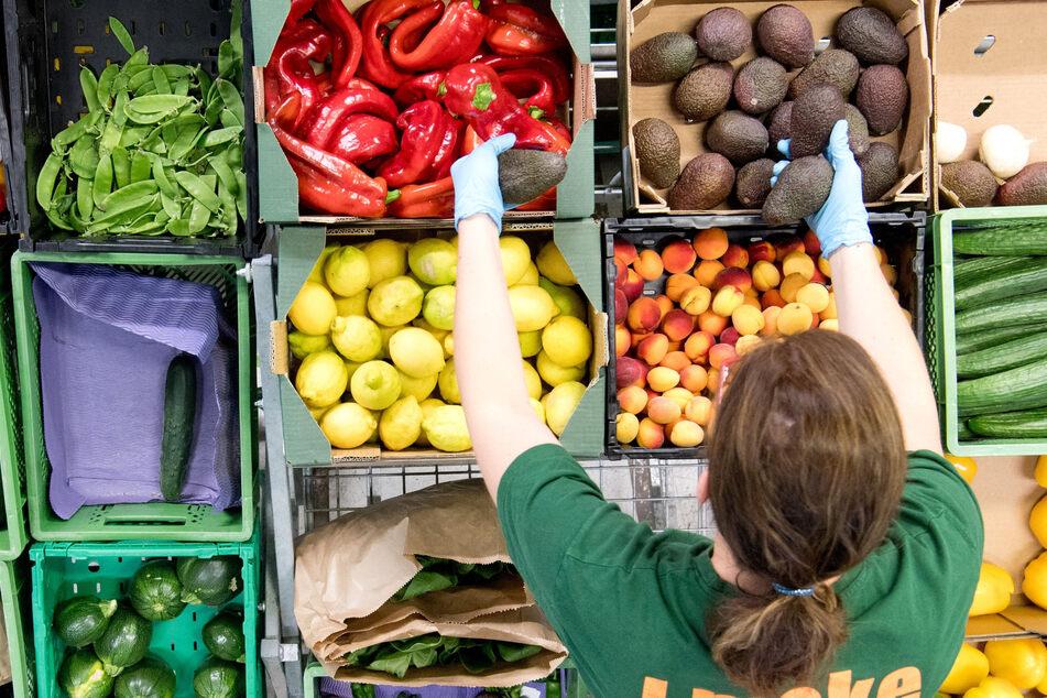 """Mitarbeiter vom Bio-Lieferanten """"Gemüsekiste"""" packen Obst und Gemüse in grüne Kisten. (Archivbild)"""