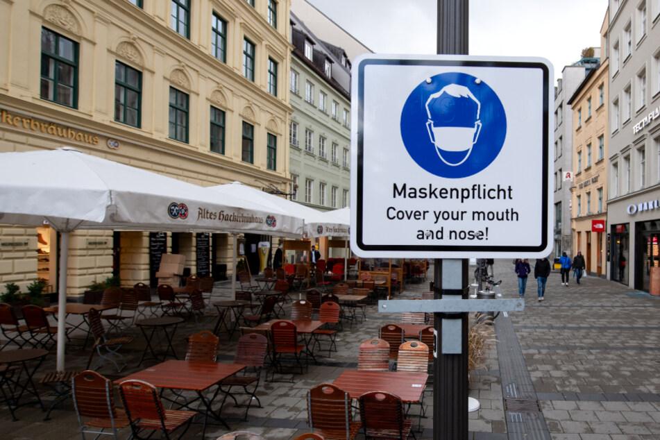 """Ein Hinweisschild mit der Aufschrift """"Maskenpflicht - Cover your mouth and nose!"""" steht in einer Fußgängerzone in der Münchner Innenstadt."""