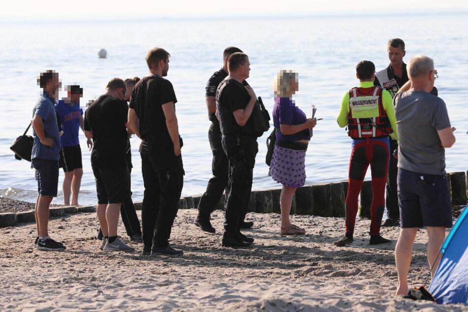 Einsatzkräfte und Badegäste stehen am Ostseestrand, um nach dem vermissten Schwimmer zu suchen.