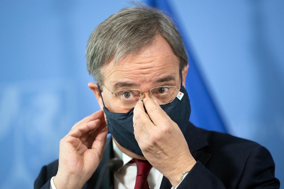 Armin Laschet (CDU), Ministerpräsident von Nordrhein-Westfalen, setzt nach einer Pressekonferenz seine Maske auf.