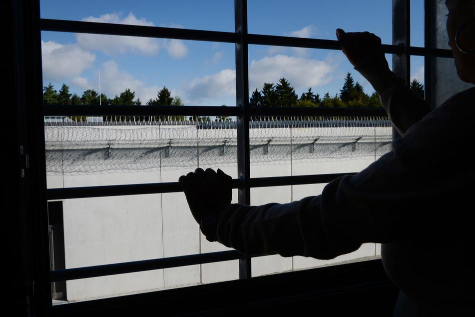 Ein Häftling steht in einem vergitterten Fenster in einer Zelle im Gefängnis (Symbolbild).