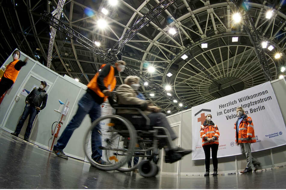 Eine Frau im Rollstuhl wird in das neu eröffnete Corona-Impfzentrum im Velodrom Stadion geführt.