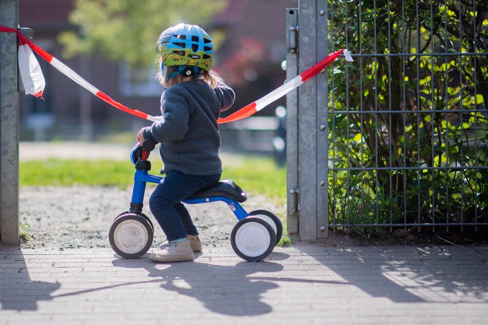 Ein Kind steht vor einem abgesperrten Spielplatz (Archivbild).