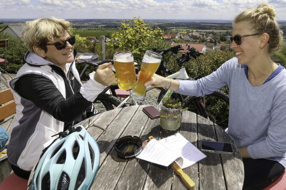 Mutter und Tochter sitzen im Biergarten und prosten sich mit einem Glas Bier zu. Im Südwesen soll es bald noch mehr Corona-Lockerungen geben. (Symbolbild)