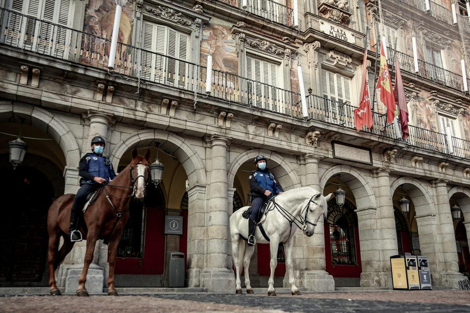 Spanien, Madrid: Berittene Polizisten patroullieren auf dem Plaza Mayor, nach dem Inkrafttreten neuer Beschränkungen.