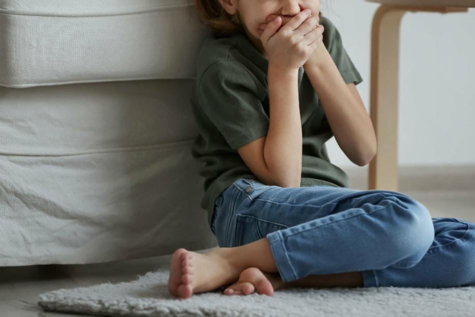Ein kleines Mädchen sitzt traurig auf dem Boden. (Symbolbild)