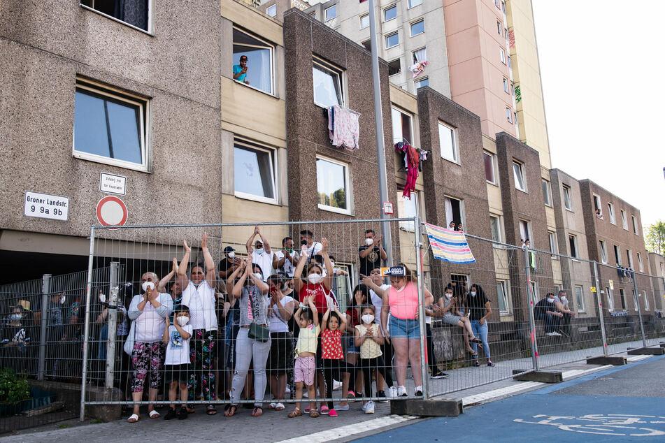 Bewohner von einem in Quarantänte gestellten Wohnkomplex stehen am Zaun und klatschen während einer Kundgebung.