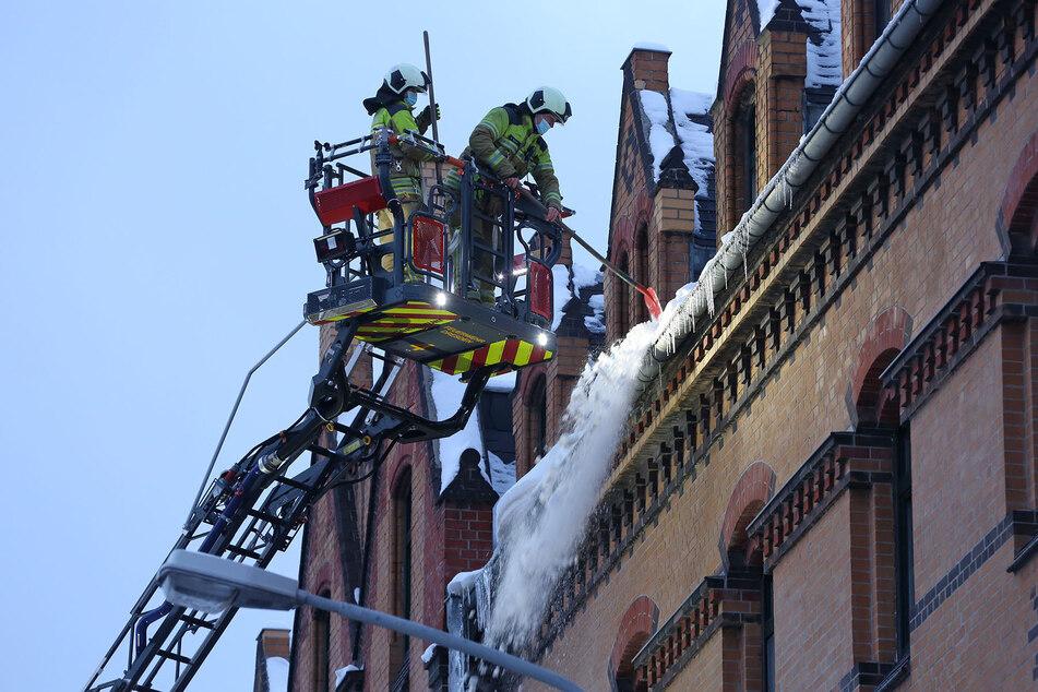 Feuerwehrleute entfernten das Eis und den Schnee vom Dach des Hauses.