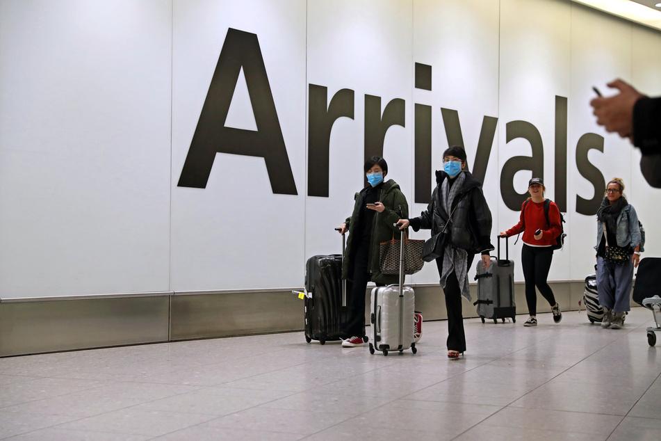 Fluggäste gehen durch die Ankunftshalle im Flughafen Heathrow.