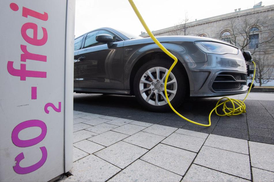 Ein Elektroauto von Audi wird mit einem Kabel an einer E-Ladesäule aufgeladen.
