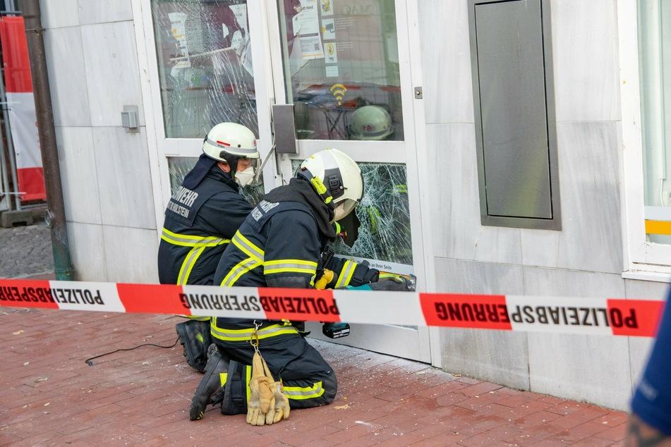 Einsatzkräfte der Feuerwehr sichern die demolierte Eingangstür der Bankfiliale.